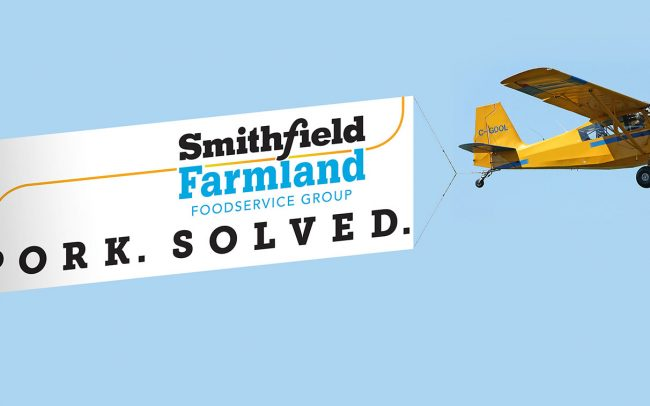 An airplane pulls a giant banner for foodservice client Smithfield through the sky for branding to the crowds below.