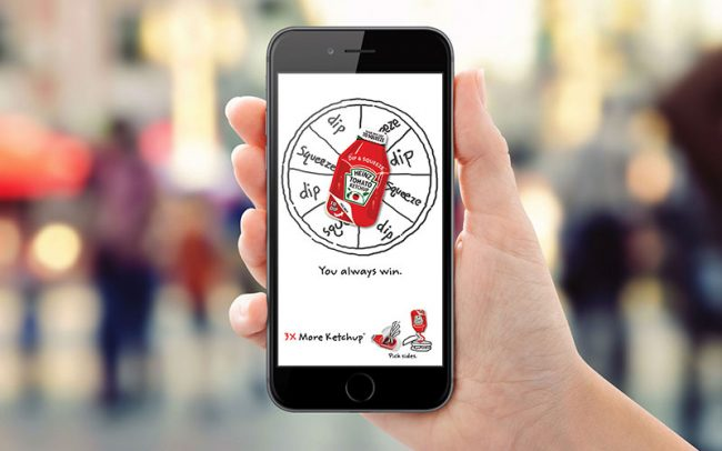 A hand holds an iphone with an interactive digital ad on the screen promoting Heinz's Dip and Squeeze ketchup.