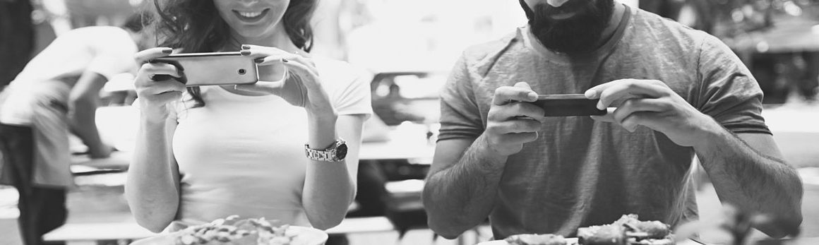 A male and female look at their iphones while sitting beside each other at an al fresco dining area.