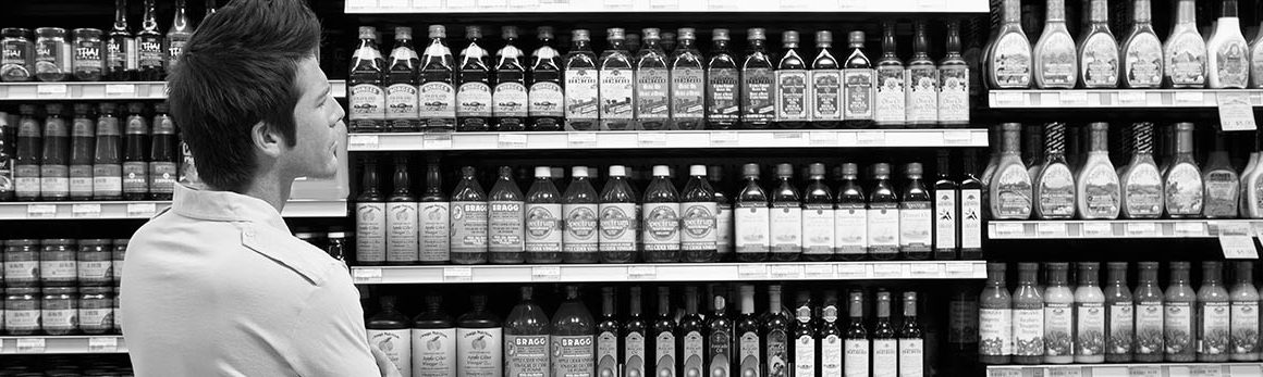 A perplexed man looks over a shelf full of various options of vinegars, condiments and more.