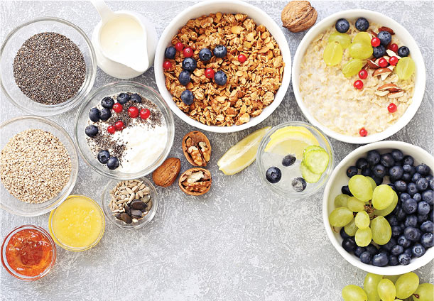 An overhead shot of various grains, spices, fruits and nuts. Bowls of cereal and of oatmeal are also shown.