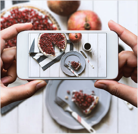 Point-of-view shot as hands hold an iphone to take a photo of a berry pie and pomegranates.