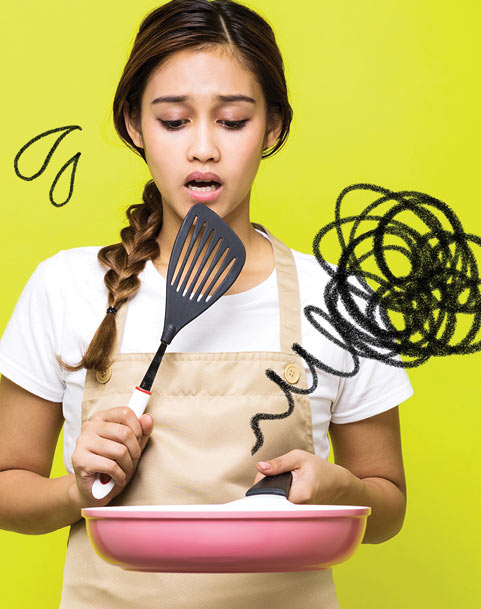 An overwhelmed young lady holds a pan and spatula. Drawings of squiggles and sweat drops represent her confusion.