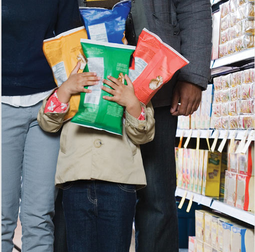 A young boy walks down a grocery aisle with two adults. His face is blocked by the four giant bags of snacks he is carrying.