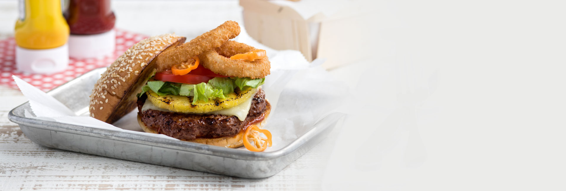 A gourmet burger with a pineapple slice and onion rings, served on a metal plate sits on a wooden table.