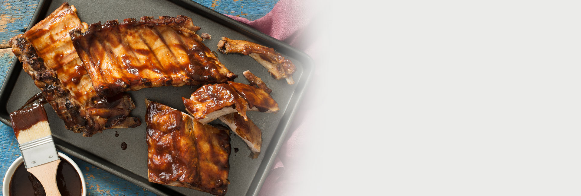 An overhead shot of juicy barbecue ribs on a pan with a brush with sauce sitting next to it.