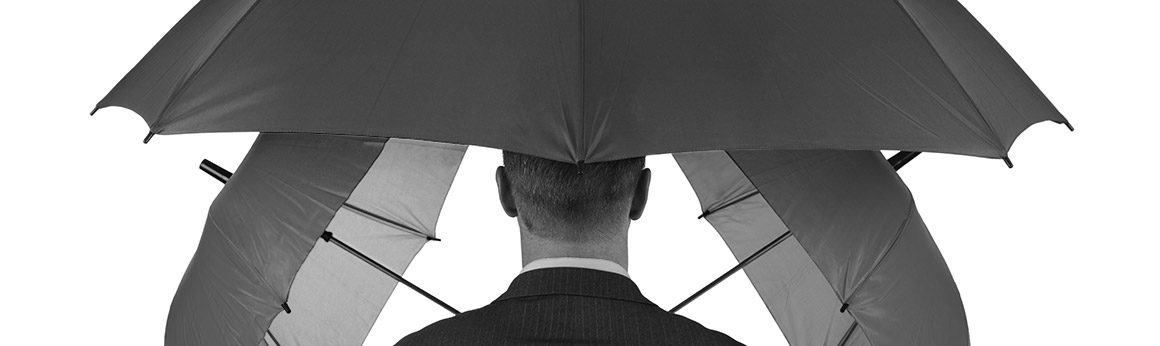 A man in a business suit surrounded by three opened umbrellas.