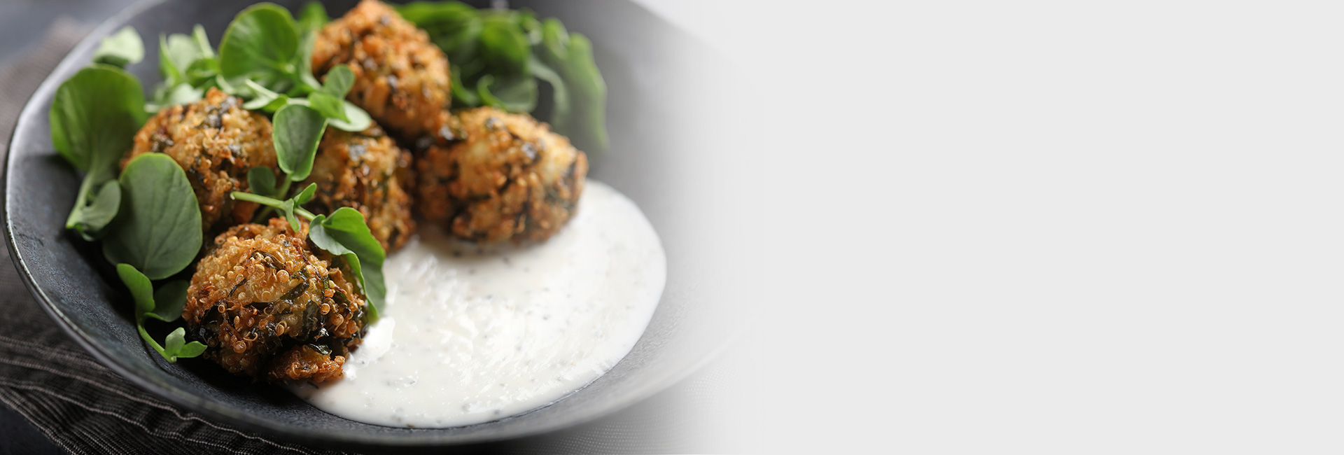 Fried falafel on a gray plate amidst various greens and a dollop of white sauce.
